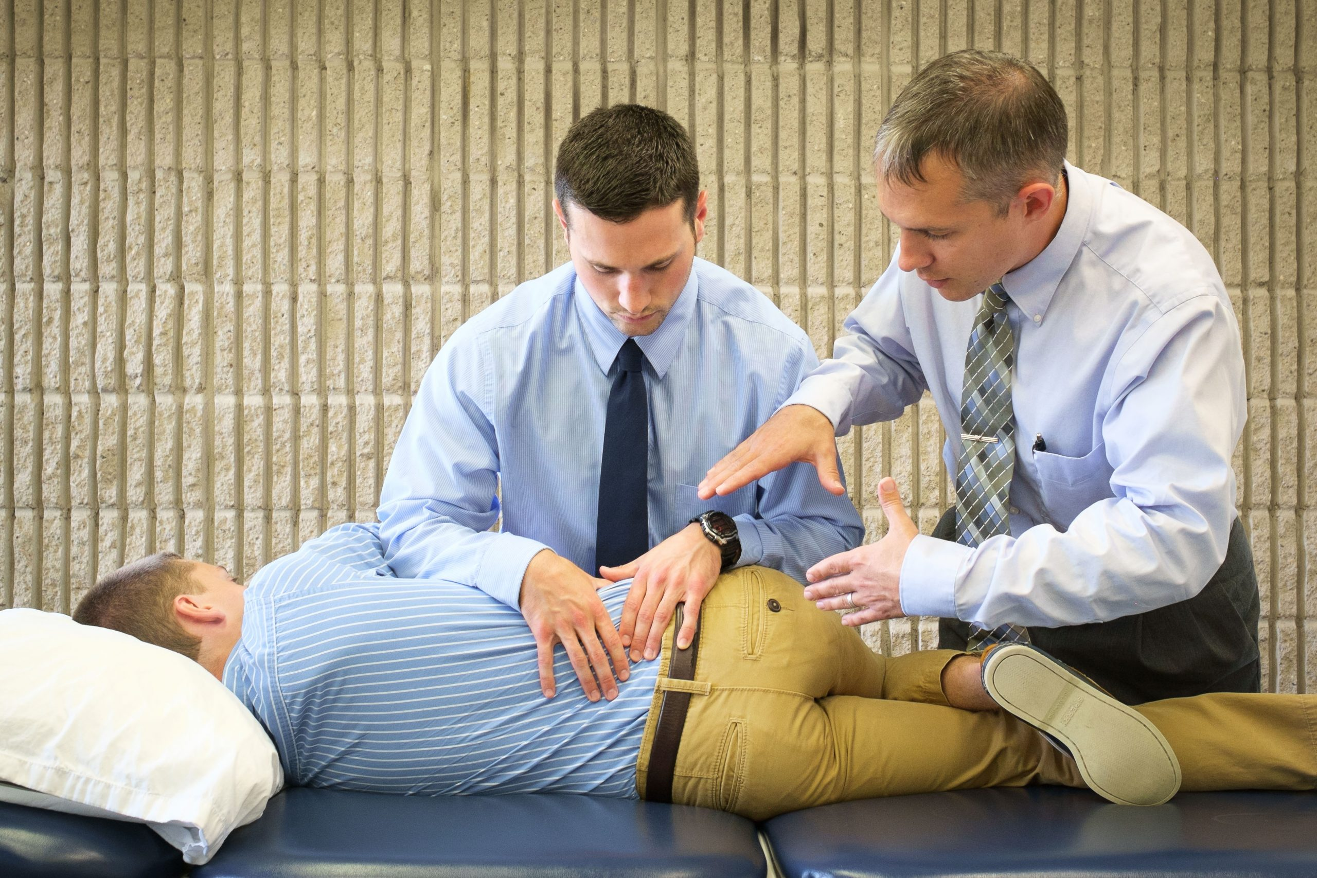 demonstrating a physical therapy exercise with faculty supervision